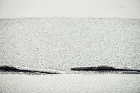 A minimalistic background image of the car's windshield covered with a layer of snow.