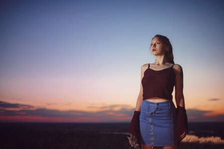 Red-haired girl is standing on the brink of a precipice against the backdrop of a beautiful sunset sky. Grunge style of clothes. Flowers in hand. Standard-Bild