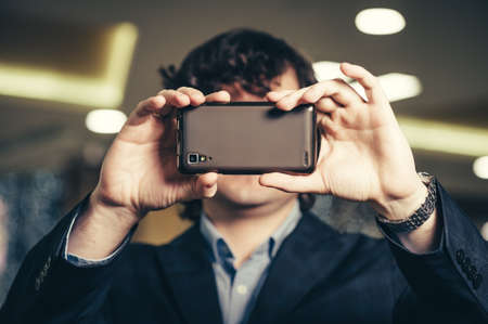 Business man looking at smartphone screen. Guy hides behind the mobile phone. Smartphones have entered our lifestyle.