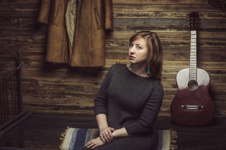 Vintage portrait of beautiful stylish girl with turquoise earrings in old wooden hut with guitar and coat on background. Foto de archivo