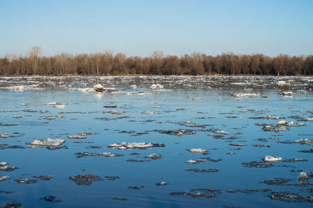Ice floats down river. Background image of melting ice. Thawing of ice in spring season. Blue sky reflected in river water.