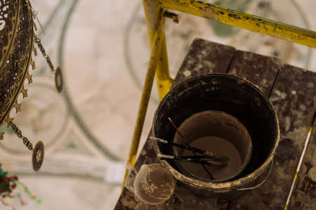 Bucket and paints on scaffolding in church during wall painting. Beautiful interior of temple in style of Byzantine architecture, Barnaul city, 24 july 2017. Editorial
