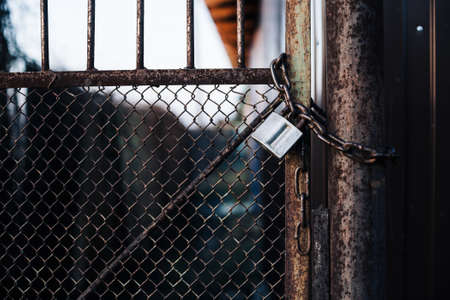 Gates with mesh on lock in iron fence. Metal gate with grid is fortified with diagonal reinforcement. Background image of steel rough gate with lock on chain. Reklamní fotografie