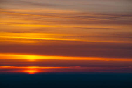 Big red sun circle rises out from behind dark horizon on background varicolored clouds of warmly shades. Beautiful background of dawn on picturesque cloud sky.