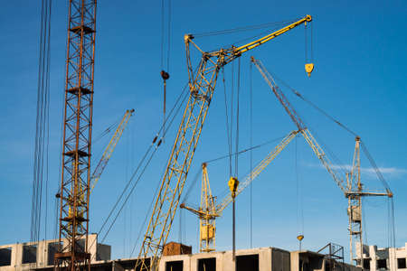 Big tower cranes above buildings under construction against blue sky. Background image of construction close-up with copy space. Build of city. Stockfoto