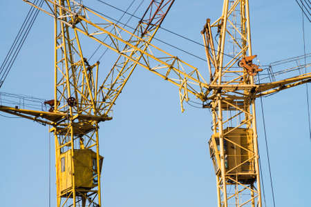 Big tower cranes against the blue sky. Background image of construction equipment close-up with copy space. Build of city.