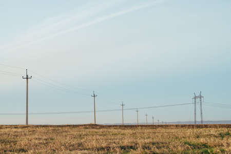 Atmospheric landscape with power lines in yellow field under blue sky. Background image of electric pillars with copy space. Wires of high voltage above ground. Electricity industry.