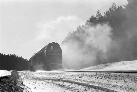 Black locomotive rides on railroad in winter forest on film. Train in cloud of hot steam. Old carriage. Atmospheric scanned analog photography with grain and scratch. Lomography of snowy railway.