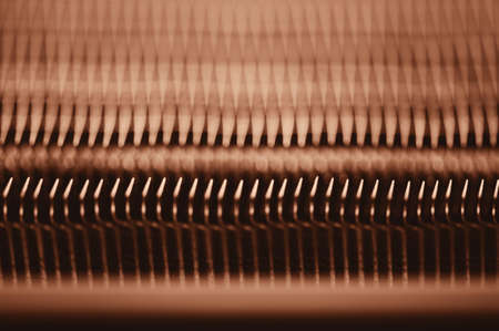 Detailed texture of engine water cooling radiator. Background image of orange automobile part with copy space close up.