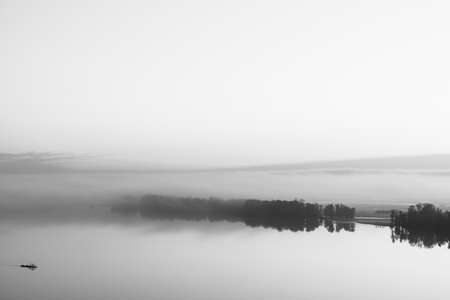 Broad river flows along diagonal shore with silhouette of forest and thick fog in grayscale. Tree drifts with flow. Minimalistic monochrome landscape of majestic nature. Morning milky atmosphere. 版權商用圖片 - 113087684