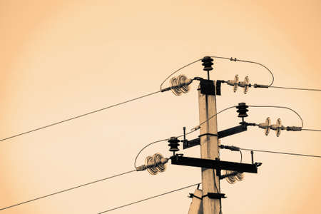 Power lines on background of sky close-up. Electric hub on pole in monochrome. Electricity equipment with copy space. Wires of high voltage in sky. Electricity industry. Sepia tone.