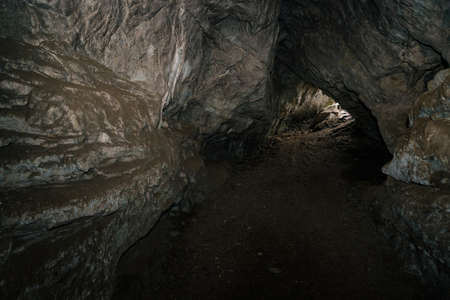 Beautiful cave. View from inside dark dungeon. Textured walls of cave. Background image of underground. Dampness inside cave. Light at end of tunnel.