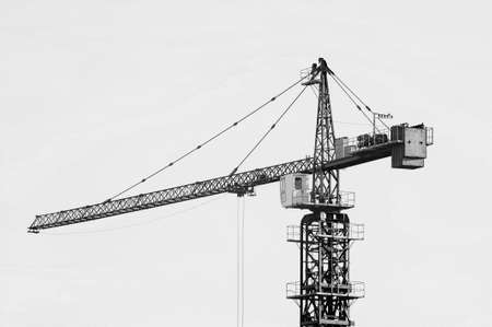 Big tower crane against sky in grayscale. Background of construction equipment close-up with copy space. Build of city in monochrome.