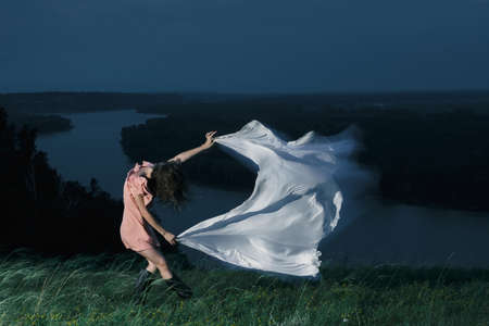 Amazing girl dancing in pink dress with big white shawl at night on background of river. Beautiful female dancer with good mood in dusk. Unimaginable mystic dance on nature in twilight. Фото со стока