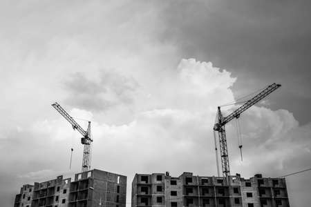 Cranes above unfinished multistorey panel building on background of cloudy sky with copy space in grayscale. Process of construction of apartment building in overcast weather close up in monochrome. 版權商用圖片