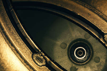 Unusual robotic eye in steampunk style. Focused robot look. Golden background pattern close-up. Banque d'images
