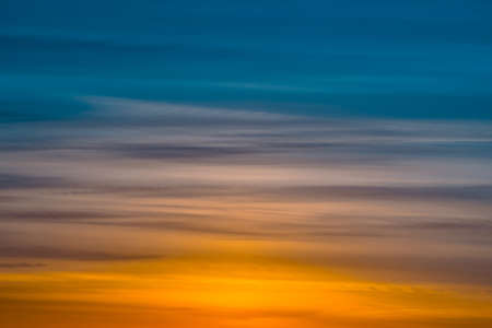 Varicolored striped dawn sky with shades of blue, cyan, cobalt, pink, purple, magenta colors. Horizontal lines of picturesque clouds. Atmospheric background image of warm sky.