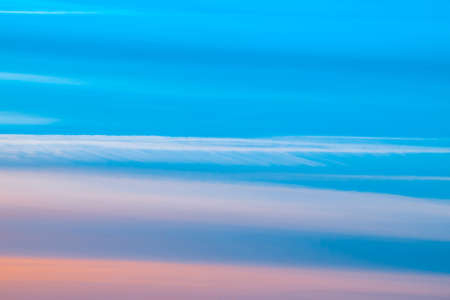Varicolored striped surreal sky with shades of blue, cyan, cobalt, pink colors. Horizontal lines of smooth clouds. Atmospheric background image of tender sky. Фото со стока