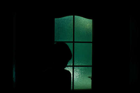 Dark silhouette of kid behind glass in supernatural green light. Locked alone in room behind door on Halloween. Nightmare of child with aliens, monsters and ghosts. Evil in home. Inside haunted house.