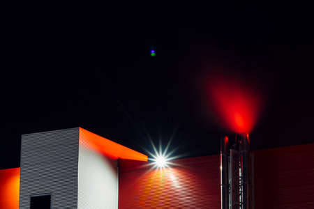 Red office building with smoke from pipe in night. Modern architecture with copy space on dark sky with lens flare. Industrial facility close up. View on below on big red wall. Shine cloud above roof.