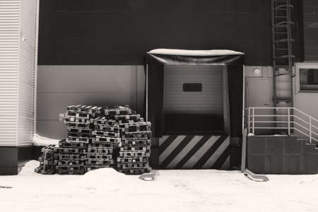 Cargo lift for storage with white black diagonal lines warning sign in grayscale. Wooden pallets on snow. Door for loading goods with copy space. Wall of warehouse in winter. Monochrome building.