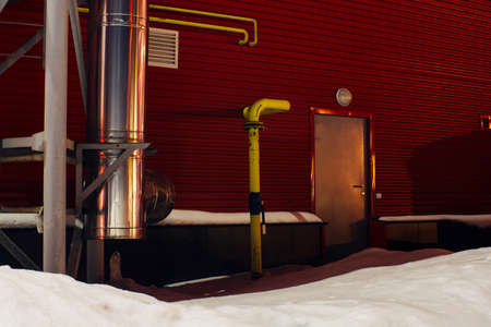 Back door in industrial building. Entrance to lab. Secret laboratory in snowy terrain. Protected area with yellow gas pipes. Iron door in red wall. Guarded territory. Security zone. Restricted area.