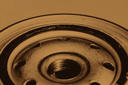 Monochrome background image of oil filter close up. Art macro photography of auto part in sepia tones. Archivio Fotografico