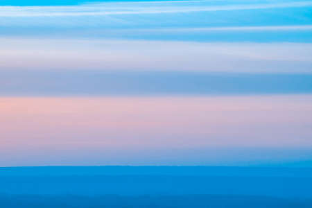 Varicolored striped surreal sky with shades of blue, cyan, pink colors with land. Horizontal lines of smooth clouds. Atmospheric background image of tender sky. Фото со стока