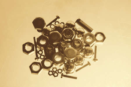 Art monochrome background from bolts and nuts close up in blue backlight. Macro photography of handful of fasteners in sepia tones.