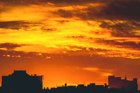 Cityscape with vivid fiery dawn. Amazing warm dramatic cloudy sky above dark silhouettes of city buildings. Orange sunlight. Atmospheric background of sunrise in overcast weather. Copy space.