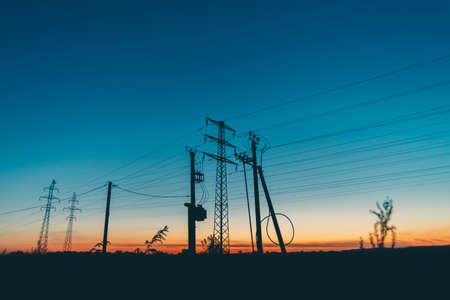 Hoogspanningslijnen in veld op zonsopgang achtergrond. Silhouetten van palen met draden bij dageraad. Kabels van hoogspanning op warme oranje blauwe lucht. Energie-industrie bij zonsondergang. Veel kabels in pittoreske levendige lucht. Stockfoto