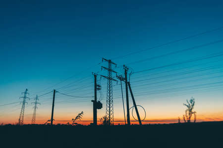 Líneas eléctricas en campo sobre fondo de amanecer. Siluetas de postes con cables al amanecer. Cables de alta tensión en el cálido cielo azul anaranjado. Industria de la energía al atardecer. Muchos cables en un pintoresco cielo vivo. Foto de archivo