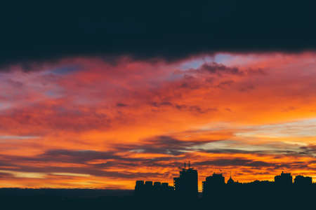 Cityscape with wonderful varicolored vivid dawn. Amazing dramatic multicolored cloudy sky above dark silhouettes of city buildings. Atmospheric background of sunrise in overcast weather. Copy space.