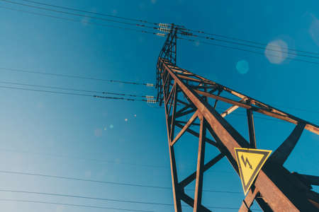 Power lines on background of blue sky close-up. Electric hub on pole. Electricity equipment with copy space. Wires of high voltage in sky. Electricity industry. Tower with lightning warning sign. Stock Photo