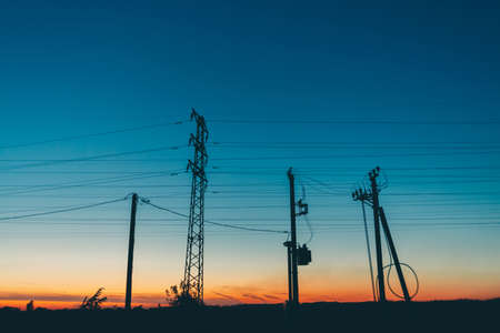 Power lines in field on sunrise background. Silhouettes of poles with wires at dawn. Cables of high voltage on warm orange blue sky. Power industry at sunset. Many cables in picturesque vivid sky.