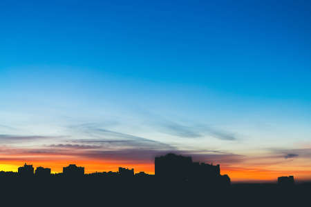 Cityscape with wonderful varicolored vivid dawn. Amazing dramatic blue sky with purple and violet clouds above dark silhouettes of city buildings. Atmospheric background of orange sunrise. Copy space.