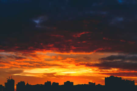 Cityscape with wonderful varicolored vivid fiery dawn. Amazing dramatic multicolored cloudy sky. Dark silhouettes of city buildings. Atmospheric background of sunrise in overcast weather. Copy space.