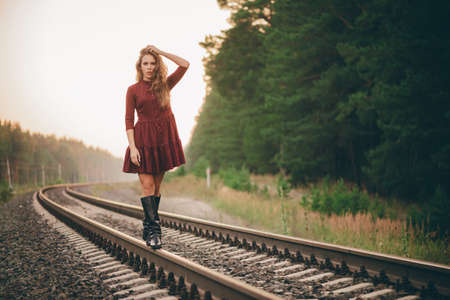 Beautiful dreamy girl with curly natural hair enjoy nature in forest on railway. Dreamer lady in burgundy dress walk on railroad. Inspired girl balancing on train rail at dawn. Sun in hair in autumn.