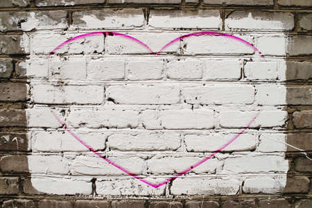 Pink drawn heart on brick wall with white paint close-up. Mock up. Urban background with pink painted heart. Imperfect exterior with love symbol graffiti. Valentine day image. Unideal brickwork.