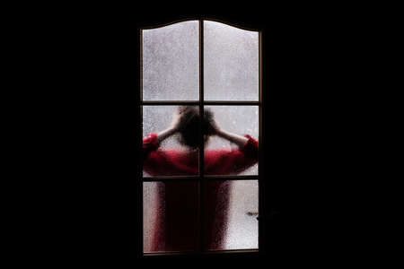 Dark silhouette of girl in red behind glass. Locked alone in room behind door on Halloween. Nightmare of child with aliens, monsters and ghosts. Evil in home. Inside haunted house. Supernatural.