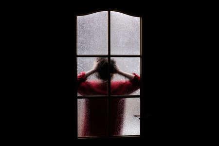 Dunkle Silhouette des Mädchens in Rot hinter Glas. An Halloween allein im Zimmer hinter der Tür eingesperrt. Albtraum des Kindes mit Außerirdischen, Monstern und Geistern. Das Böse im Haus. Im Geisterhaus. Übernatürlich. Standard-Bild
