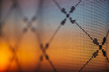 Wonderful vivid dawn from window through patterned curtain. Amazing warm sky behind silhouettes of tulle texture. Orange sunlight. Cosiness textured colorful background with sunrise. Copy space. Stock fotó