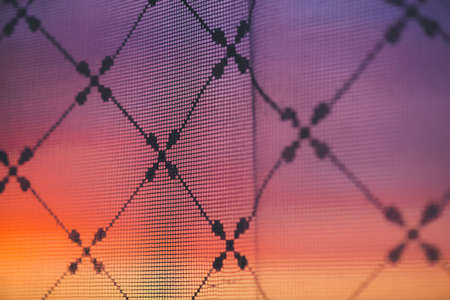 Amazing romantic sunset in window behind silhouettes of tulle texture. Wonderful pink orange violet dawn sky from window through patterned curtain. Cosiness background of scenic sunrise. Copy space.