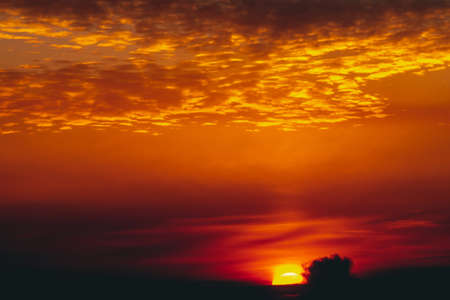 Sunny shine on clouds. Wonderful vivid dawn. Beautiful calm orange sunset. Scenic surreal sunrise. Amazing red cloudy sky. Picturesque sundown. Atmospheric cloudscape. Circle of sun above horizon. Stock fotó