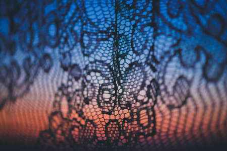 Amazing romantic sunset in window behind silhouettes of tulle texture. Wonderful grapefruit blue dawn sky from window through patterned curtain. Cosiness background of scenic sunrise. Copy space.