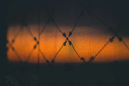 Amazing romantic vivid sunset in window behind silhouettes of tulle texture. Wonderful warm orange dawn sky from window through patterned curtain. Cosiness background of scenic sunrise. Copy space.