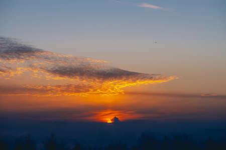 Sunny shine on clouds. Wonderful vivid dawn. Beautiful calm sunset. Scenic tranquil sunrise. Amazing peaceful cloudy sky. Sun above horizon. Picturesque sundown. Atmospheric cloudscape. Background.