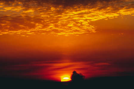Sunny shine on clouds. Wonderful vivid dawn. Beautiful calm orange sunset. Scenic surreal sunrise. Amazing red cloudy sky. Picturesque sundown. Atmospheric cloudscape. Circle of sun above horizon. Фото со стока