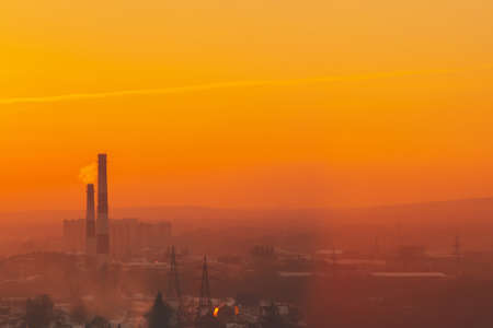 Smog among silhouettes of buildings on sunrise. Smokestack in dawn sky. Environmental pollution on sunset. Harmful fumes from stack above city. Mist urban background with warm orange yellow sky.