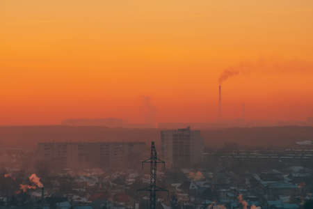 Power lines in city on dawn. Silhouettes of urban buildings among smog on sunrise. Cables of high voltage on warm orange yellow sky. Power industry at sunset. City power supply. Mist urban background. Фото со стока